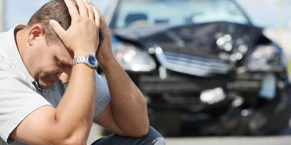 man-with-hands-on-head-near-wrecked-car-in-background